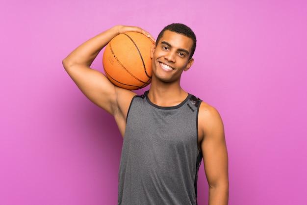 Hombre joven deporte con pelota de baloncesto sobre pared púrpura aislado