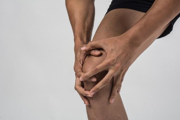 Hombre joven del deporte con las piernas atléticas fuertes que sostienen la rodilla con sus manos en dolor después de sufrir lesión del ligamento aislada en blanco.