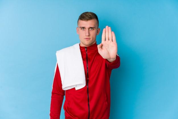 Hombre joven del deporte que se coloca con la mano extendida que muestra la señal de stop, previniéndole.