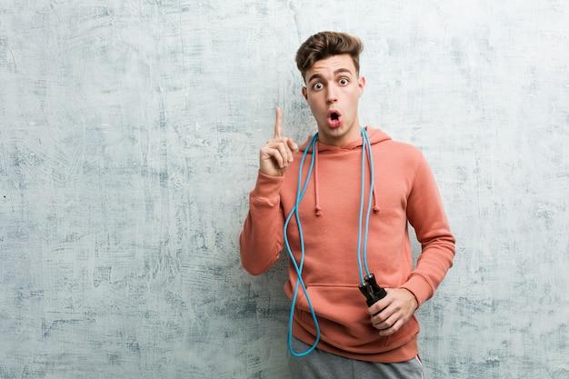 Hombre joven del deporte que sostiene una comba que tiene una gran idea, de creatividad.