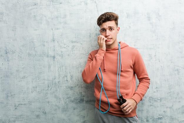 Hombre joven deporte sosteniendo una comba mordiendo las uñas, nervioso y muy ansioso.