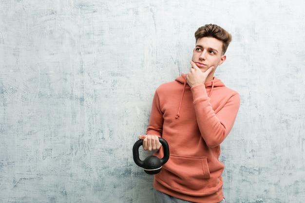 Hombre joven deporte sosteniendo una mancuerna mirando hacia los lados con expresión dudosa y escéptica.