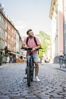 Hombre joven de los deportes en una bicicleta en una ciudad europea. el deporte en entornos urbanos.