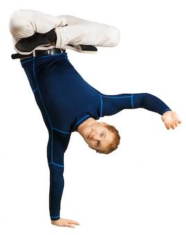 Hombre joven deportivo flexible que hace estirando ejercicios aislados en el fondo blanco
