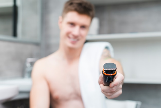 Hombre joven descamisado desenfocado con una toalla blanca sobre su hombro que da el recortador hacia la cámara