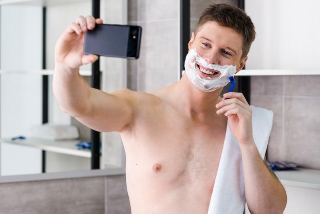 Hombre joven descamisado que afeita en el cuarto de baño que toma el selfie en smartphone