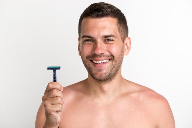 Hombre joven descamisado sonriente que sostiene la maquinilla de afeitar que se opone al fondo blanco