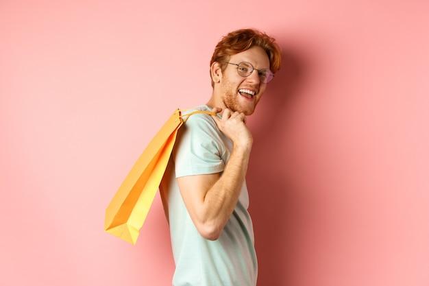 Hombre joven despreocupado con el pelo rojo y gafas caminando con bolsa de compras al hombro y sonriendo ...