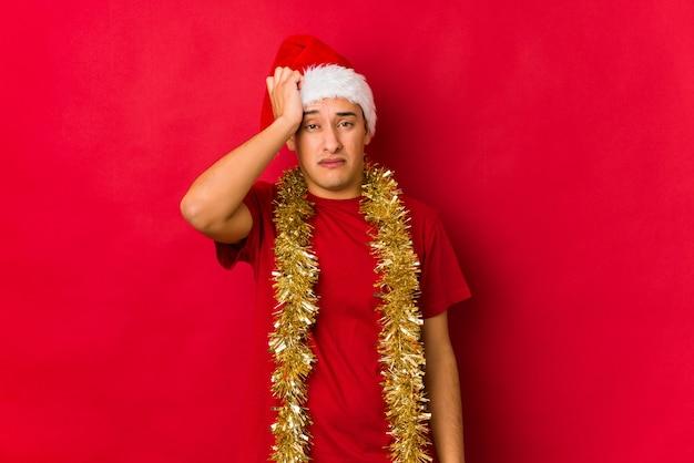 Hombre joven en el día de navidad cansado y con mucho sueño manteniendo la mano en la cabeza.