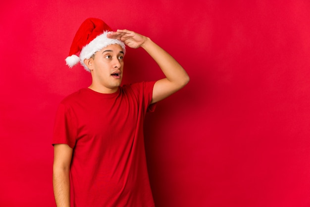 Hombre joven el día de navidad mirando lejos manteniendo la mano en la frente.