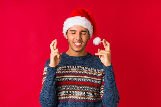 Hombre joven el día de navidad de pie con la mano extendida que muestra la señal de stop, impidiéndole.