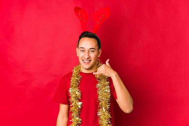 Hombre joven el día de navidad que muestra un gesto de llamada de teléfono móvil con los dedos.