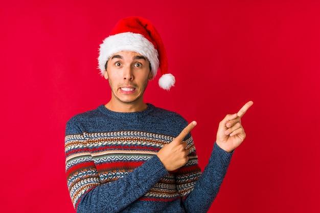 Hombre joven el día de navidad sonriendo alegremente señalando con el dedo lejos.