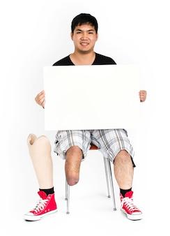 Hombre joven con discapacidad con la pierna de la prótesis que sostiene el retrato del estudio del tablero de papel en blanco