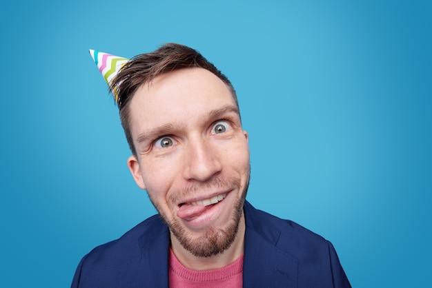 Hombre joven divertido con expresión facial loca de pie mientras se burla