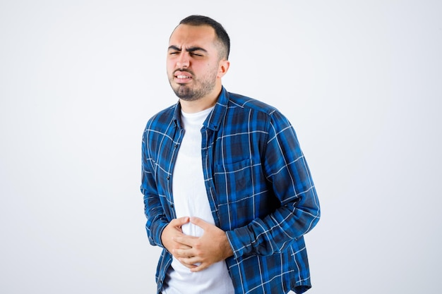Hombre joven con dolor de estómago en camisa a cuadros y camiseta blanca y mirando agotado