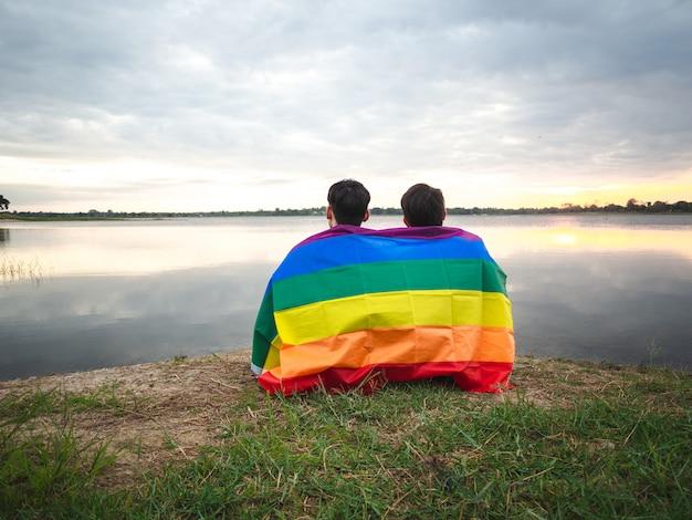 Hombre joven dos cubierto por una bandera del arco iris al lado del lago en fondo del cielo de la puesta del sol.