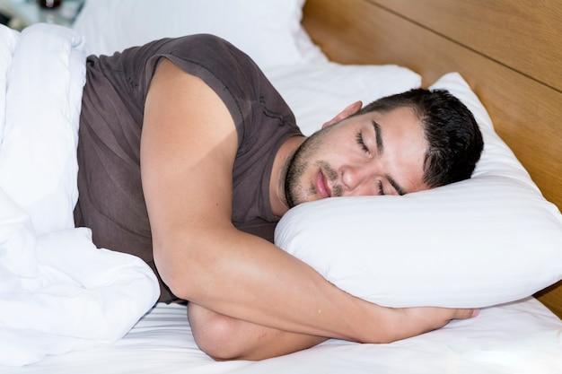 Hombre joven durmiendo en su cama