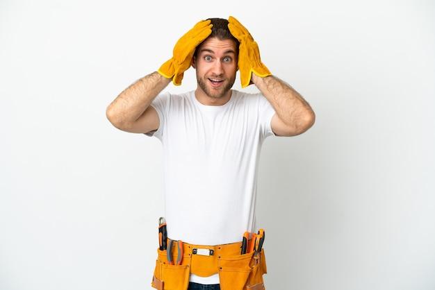 Hombre joven electricista sobre pared blanca aislada con expresión de sorpresa