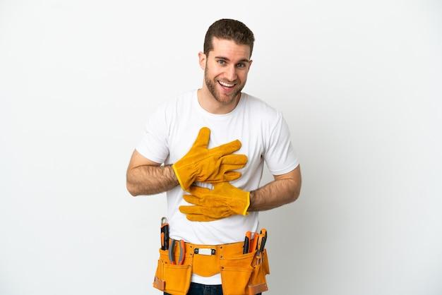 Hombre joven electricista sobre pared blanca aislada sonriendo mucho