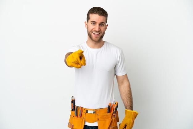 Hombre joven electricista sobre pared blanca aislada sorprendido y apuntando hacia el frente