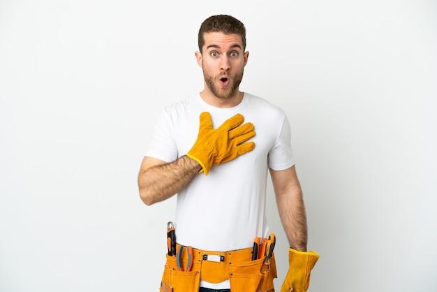 Hombre joven electricista sobre pared blanca aislada sorprendido y conmocionado mientras mira a la derecha