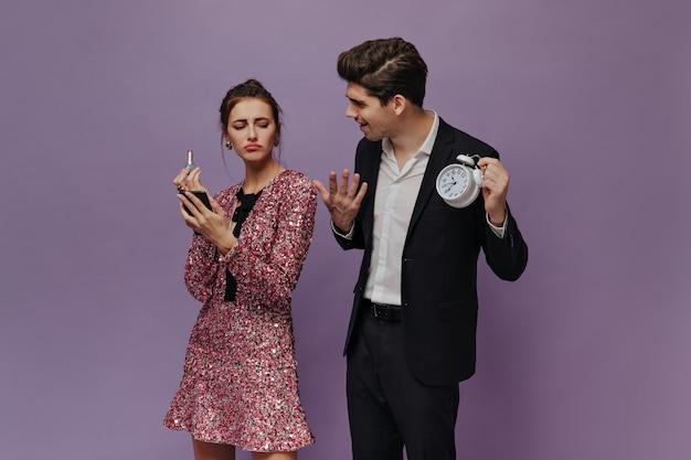 Hombre joven elegante con camisa blanca y traje negro sosteniendo con reloj y quejándose con su novia con un vestido brillante