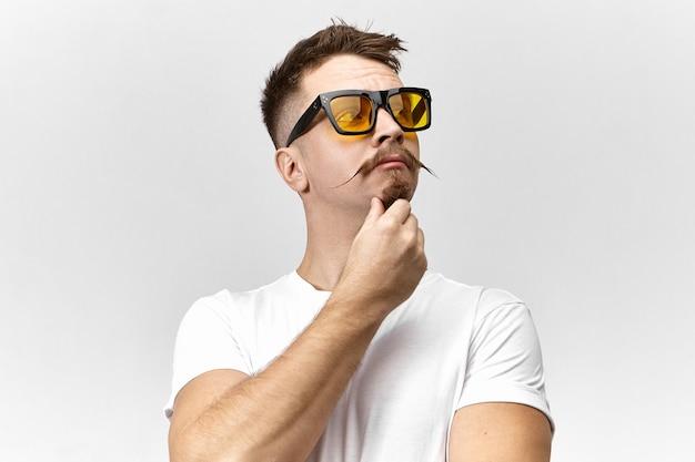 Hombre joven elegante con gafas de sol y camiseta blanca pensando