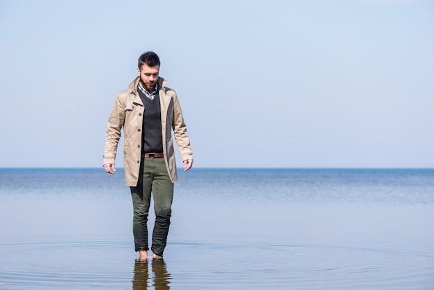 Hombre joven elegante que camina en el agua de mar poco profunda contra el cielo azul