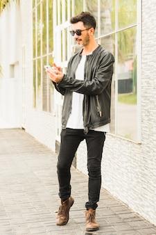 Hombre joven elegante que se coloca en la acera usando smartphone
