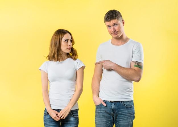 Hombre joven elegante que culpa a su novia contra fondo amarillo