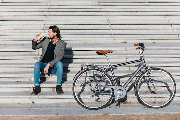 Hombre joven elegante que se sienta en escalera con café de consumición de la bicicleta