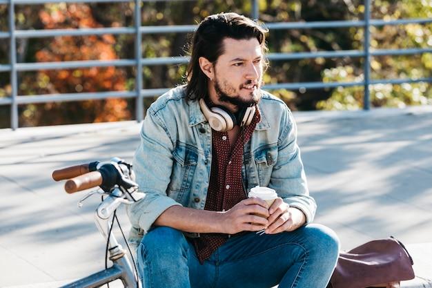 Hombre joven elegante que se sienta en el parque que sostiene la taza de café de papel para llevar en manos