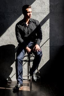 Hombre joven elegante que se sienta en taburete en luz del sol contra la pared gris