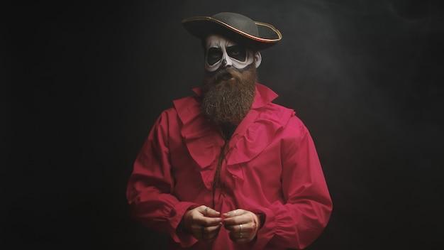 Hombre joven con un elegante sombrero disfrazado de pirata para la fiesta de halloween.