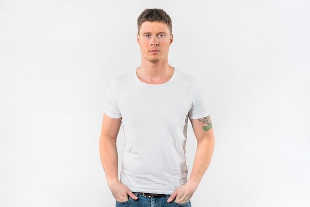 Hombre joven elegante con sus manos en bolsillo contra el fondo blanco