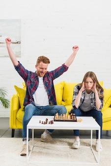 Hombre joven emocionado que celebra su éxito después de jugar el juego de ajedrez con la novia