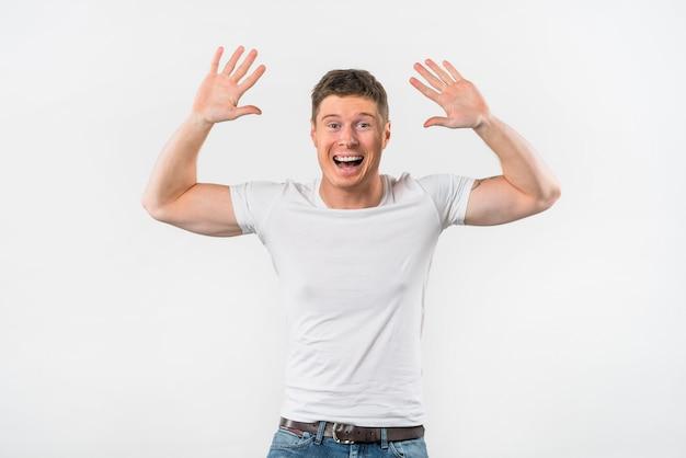 Hombre joven emocionado que levanta sus brazos para dar alta cinco contra el fondo blanco