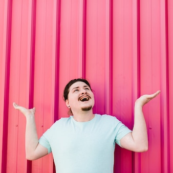 Hombre joven emocionado que mira para arriba que se encoge de hombros contra la hoja rosada del hierro acanalado