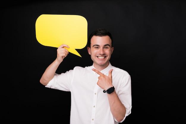 Hombre joven emocionado que señala en un discurso amarillo de la burbuja. di algo o deja un comentario.