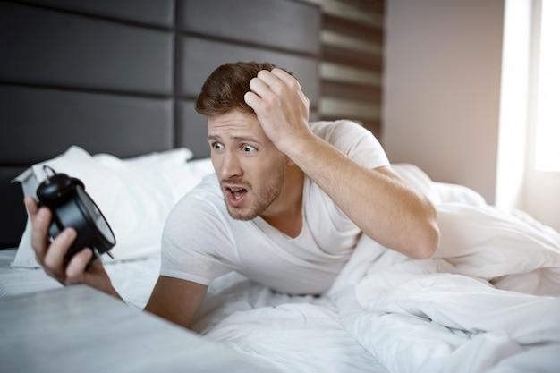 Hombre joven emocional en cama en madrugada. se durmió de más. el tipo sostiene el reloj y lo mira asustado.