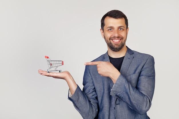 Hombre joven empresario con barba en una chaqueta apunta al carrito de la compra en su mano, mostrando con la mano y apuntando con el dedo.