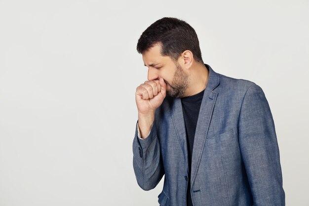 Hombre joven empresario con barba en una chaqueta, malestar y tos como síntoma de un resfriado o bronquitis.