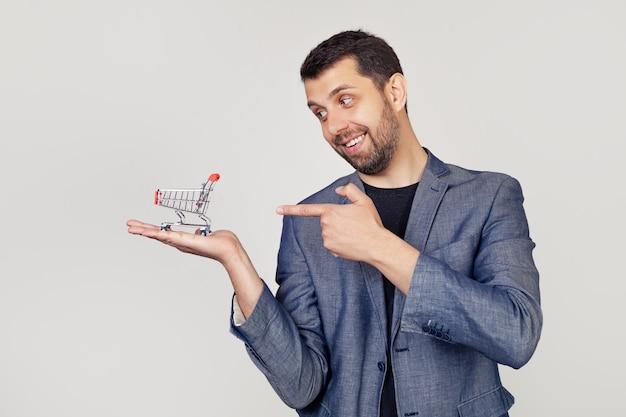 Hombre joven empresario con barba en una chaqueta mira y apunta a un carrito de compras en su mano, mostrando con la mano y apuntando con el dedo.
