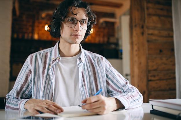 Hombre joven enfocado con anteojos y auriculares inalámbricos sentado en la mesa escuchando un seminario web, curso educativo, tomando notas.