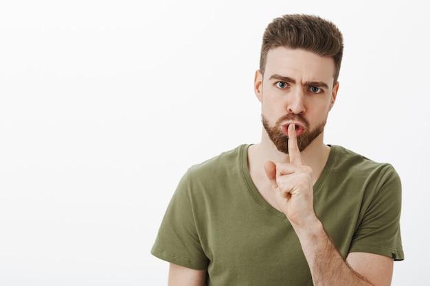 Hombre joven enojado disgustado con barba frunciendo el ceño y mirando irritado mientras callaba exigiendo guardar silencio, no hablar, sosteniendo el dedo índice en la boca mientras hacía shhh sobre la pared blanca
