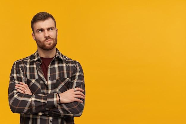 Hombre joven escéptico pensativo en camisa a cuadros con barba mantiene los brazos cruzados y pensando sobre la pared amarilla mirando hacia otro lado