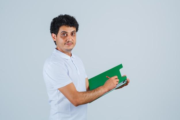 Hombre joven escribiendo algo en el cuaderno en camiseta blanca y jeans y mirando feliz, vista frontal.