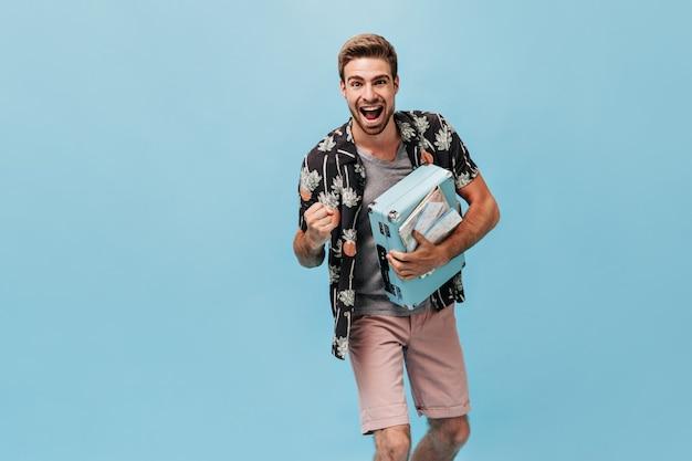 Hombre joven con estilo alegre con peinado fresco y barba en camisa de verano moderna y pantalones cortos beige con maleta azul y se regocija