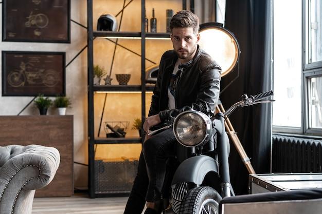 Hombre joven con estilo en chaqueta de cuero sentado en moto.
